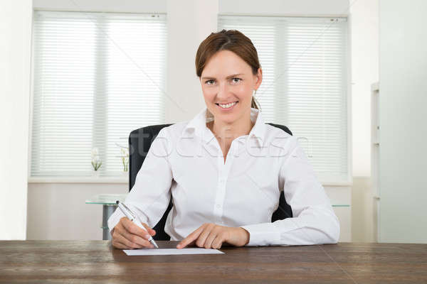 Businesswoman Signing Cheque Stock photo © AndreyPopov