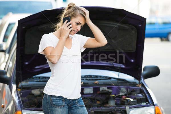 Kobieta telefonu komórkowego patrząc podziale w dół samochodu Zdjęcia stock © AndreyPopov