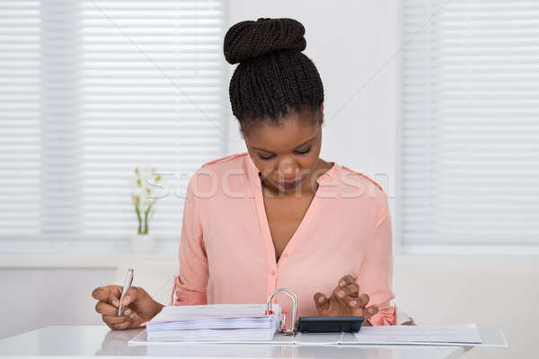 Woman Calculating Invoice With Calculator Stock photo © AndreyPopov