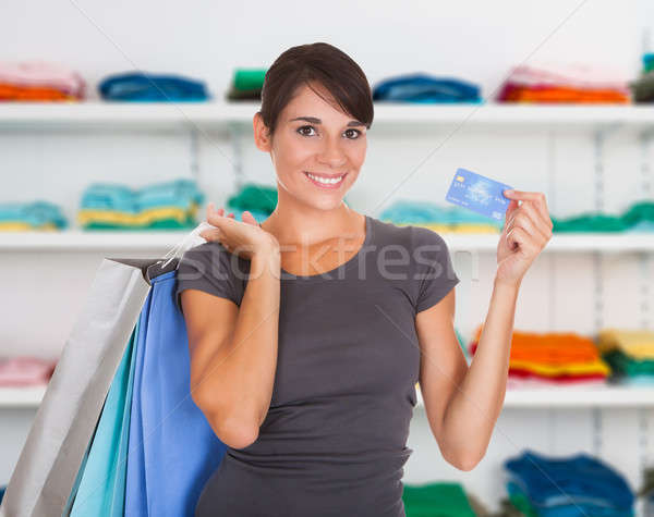 Happy Woman Holding Credit Card In Clothing Store Stock photo © AndreyPopov