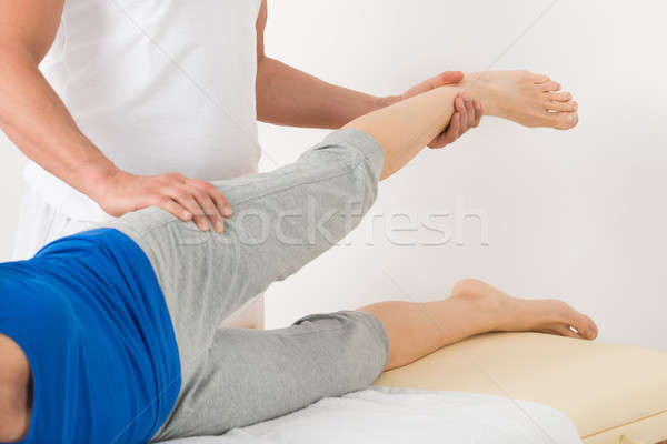 Male Therapist Giving Leg Massage To Woman Stock photo © AndreyPopov