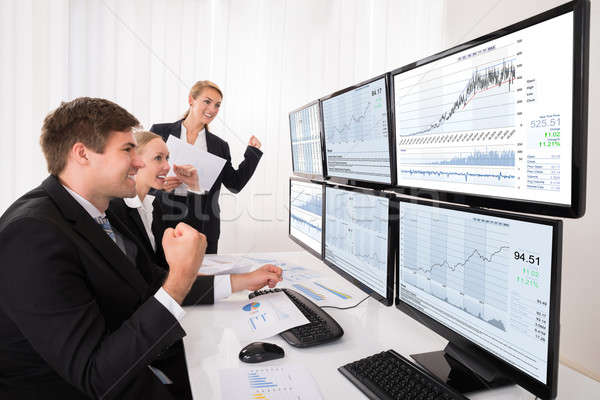 Happy Stock Market Brokers Looking At Graphs Stock photo © AndreyPopov