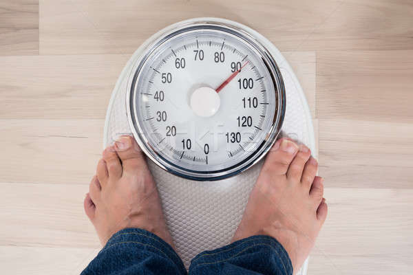 Person Standing On Weighing Scale Stock photo © AndreyPopov