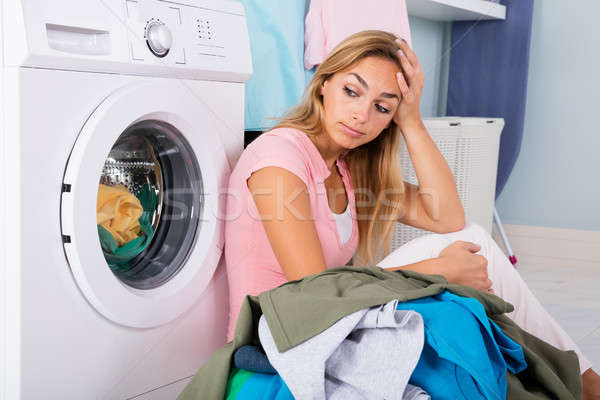 Stock photo: Unhappy Woman Looking At Clothes In Utility Room
