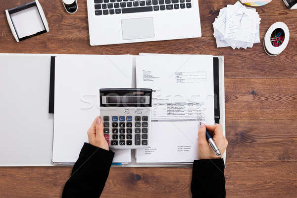 Businessperson's Hand Calculating Bill In Office Stock photo © AndreyPopov