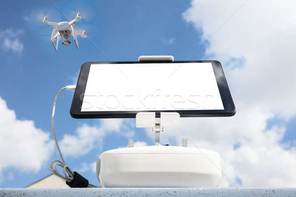 Digital tablet attached to controller while drone flying in sky Stock photo © AndreyPopov
