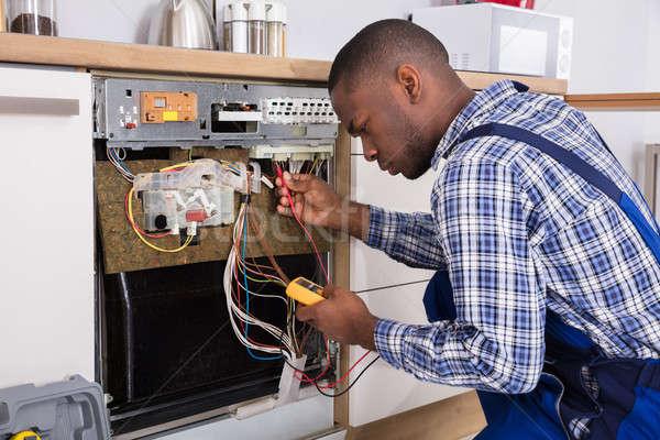 Technician Fixing Dishwasher With Digital Multimeter Stock photo © AndreyPopov