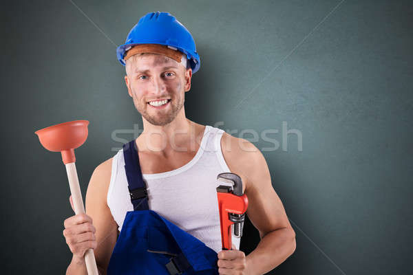 Plumber Holding Wrench And Plunger Stock photo © AndreyPopov