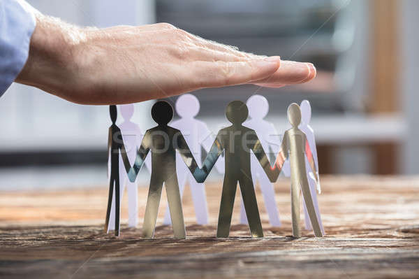 Close-up Of A Businessperson Protecting Human Cut-out Figures Stock photo © AndreyPopov