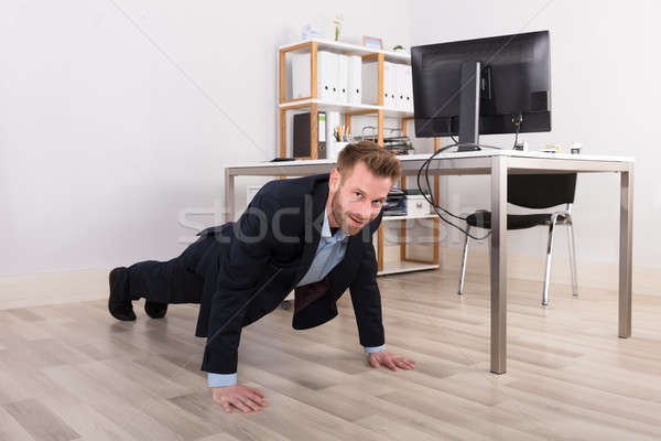 Stock photo: Businessman Doing Exercise In Office