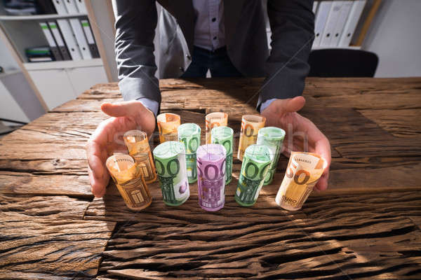 Businessperson Protecting Rolled Up Banknotes Stock photo © AndreyPopov