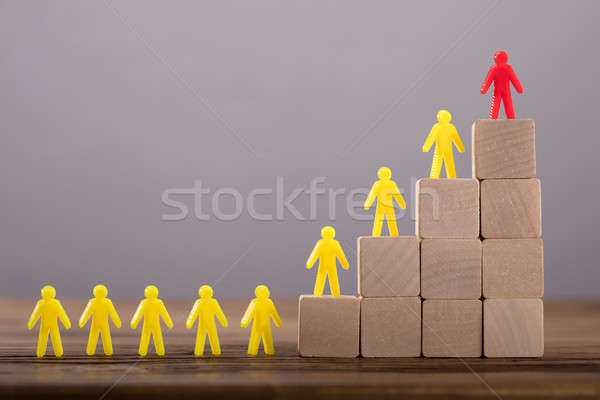 Red Figure Leading Human Figures On Top Of Wooden Blocks Stock photo © AndreyPopov