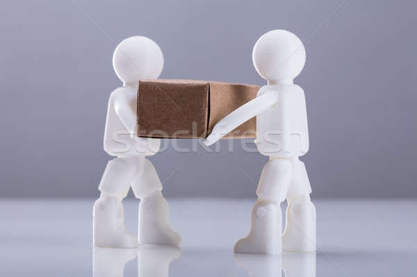 Close-up Two Human Figures Carrying Cardboard Box Stock photo © AndreyPopov