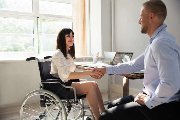 Disabled Businesswoman Shaking Hand With Her Partner Stock photo © AndreyPopov