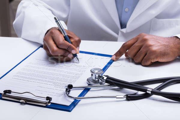 Médecin remplissage forme bureau stéthoscope stylo Photo stock © AndreyPopov