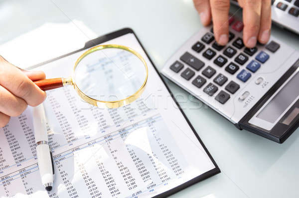 Businessman Analyzing Financial Report With Magnifying Glass Stock photo © AndreyPopov