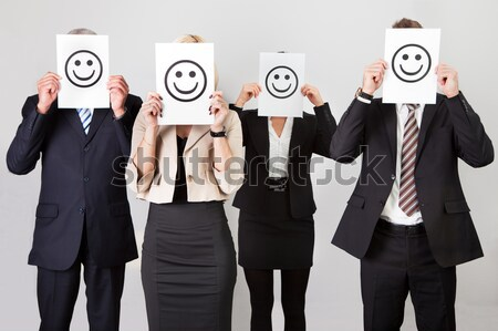 Businesspeople Holding Smiley Icon Stock photo © AndreyPopov