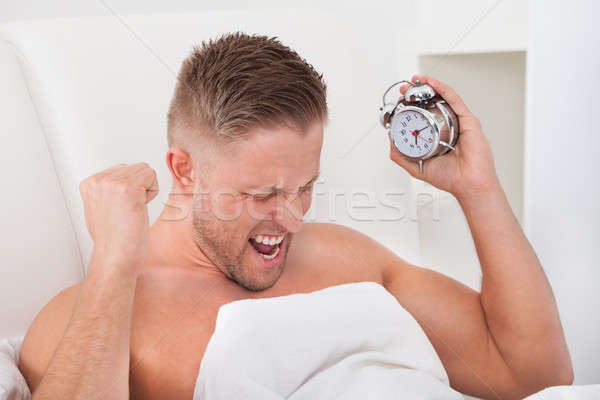 Man screaming in frustration at his alarm clock Stock photo © AndreyPopov