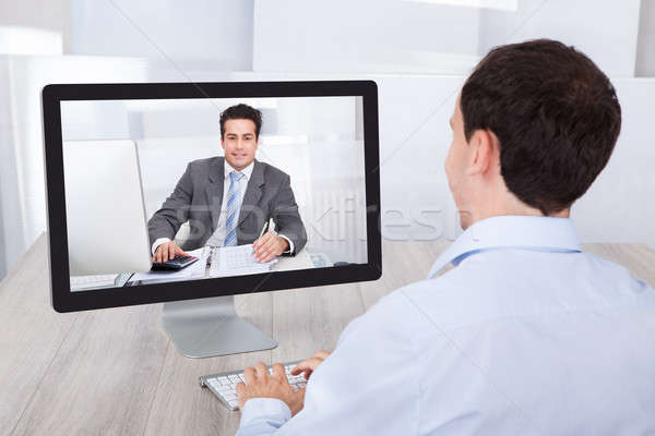 Businessman Video Conferencing With Coworker On Pc At Desk Stock photo © AndreyPopov