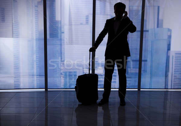 Businessman With Luggage Using Cell Phone In Office Stock photo © AndreyPopov