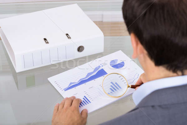 Analyst inspecting graph using magnifying glass Stock photo © AndreyPopov