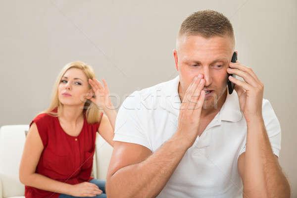 Esposa mirando marido hablar teléfono móvil curiosidad Foto stock © AndreyPopov
