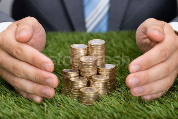 Businessman Protecting Stacked Coins On Grass Stock photo © AndreyPopov