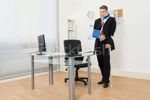 Disabled Businessman Standing With Crutches Stock photo © AndreyPopov
