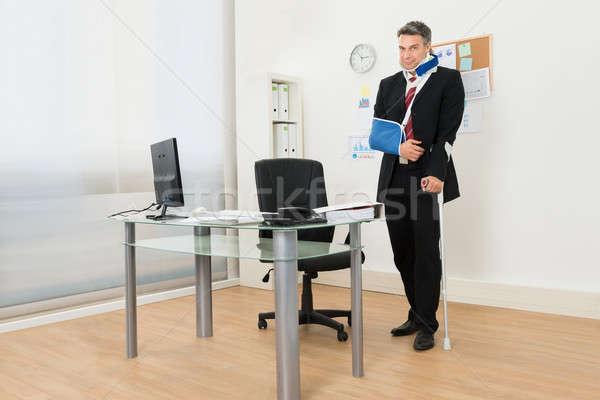 Mozgássérült üzletember áll mankók portré iroda Stock fotó © AndreyPopov