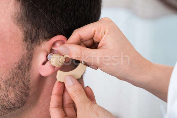 Hands Inserting A Hearing Aid Into A Man's Ear Stock photo © AndreyPopov
