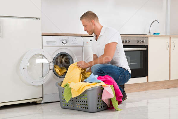 Man Putting Dirty Clothes Into The Washing Machine Stock photo © AndreyPopov