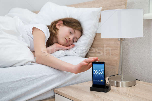 Girl On Bed Snoozing Mobile Phone Alarm Stock photo © AndreyPopov