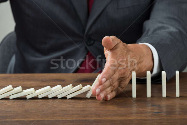 Businessman Stopping Dominoes Falling On Wooden Desk Stock photo © AndreyPopov