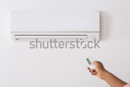 Person's Hand Holding Remote To Operate Air Conditioner Stock photo © AndreyPopov