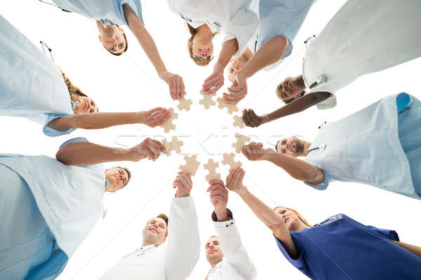 Stock photo: Medical Team Joining Jigsaw Pieces In Huddle