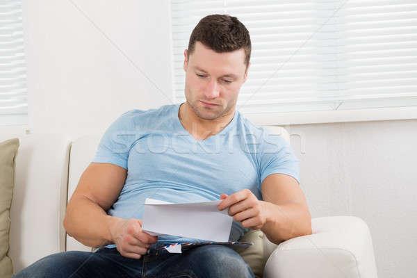 Poważny człowiek czytania list kanapie domu Zdjęcia stock © AndreyPopov