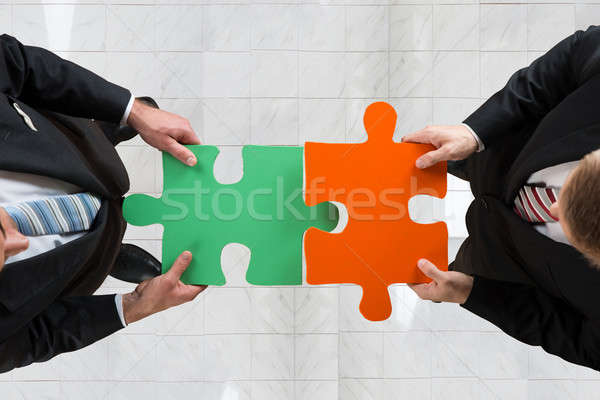Businessmen Assembling Jigsaw Puzzle Representing Teamwork Stock photo © AndreyPopov