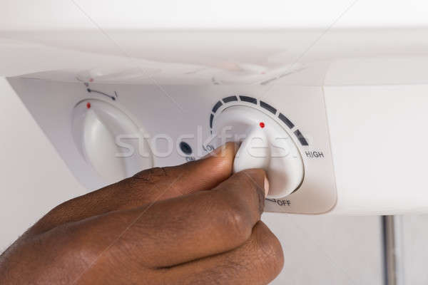 Plumber's Hand Turning The Knob Of Electric Boiler Stock photo © AndreyPopov
