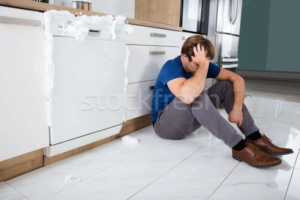 Man Sitting Next To Dishwasher Stock photo © AndreyPopov