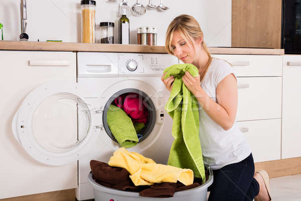 Woman Smelling Cleaned Clothes Near Washing Machine Stock photo © AndreyPopov