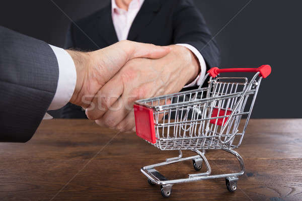 Two Businessmen Shaking Hands Near Shopping Cart Stock photo © AndreyPopov