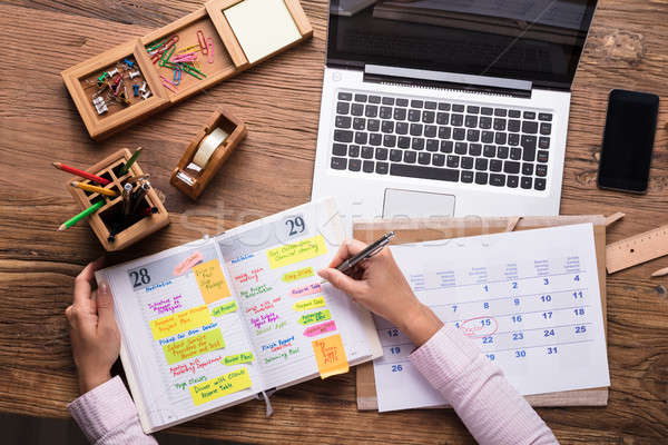 Stock photo: Businesswoman Writing Schedule In Calendar Diary