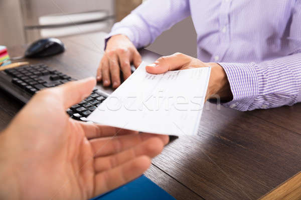 Businessman Giving Cheque To Her Colleague Stock photo © AndreyPopov
