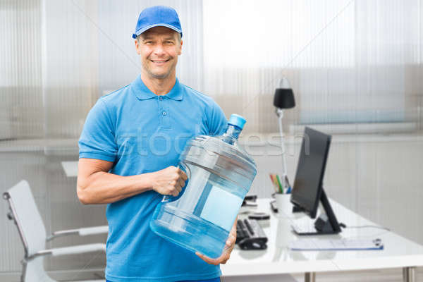 Delivery Man Holding Large Water Bottle In Office Stock photo © AndreyPopov