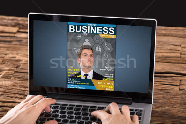 Person Looking At Magazine On Laptop Stock photo © AndreyPopov