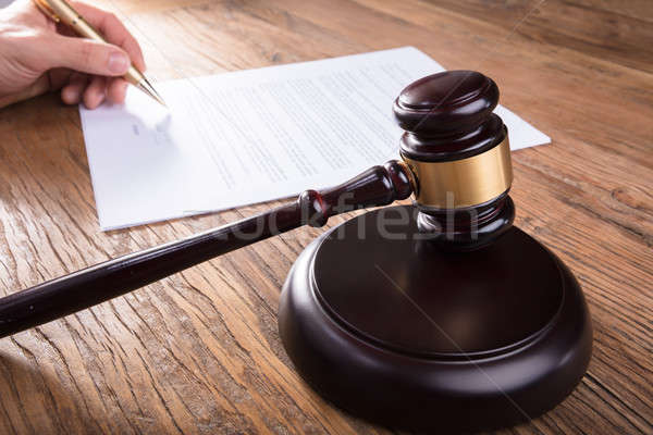 Gavel With Person's Hand Signing Legal Document Stock photo © AndreyPopov