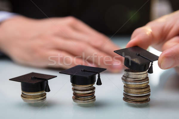 Businessperson Placing Graduation Hat Over Stacked Coins Stock photo © AndreyPopov