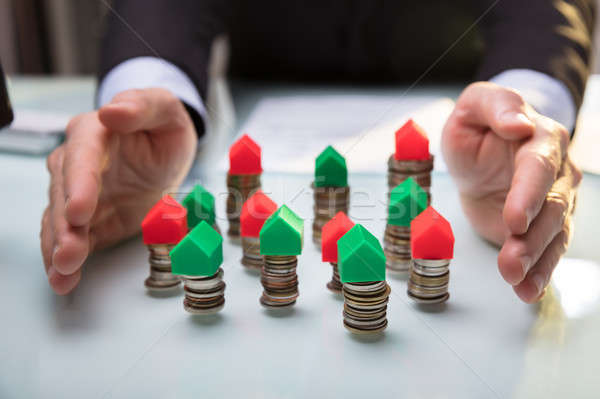 Businessperson Protecting House Models On Stacked Coins Stock photo © AndreyPopov
