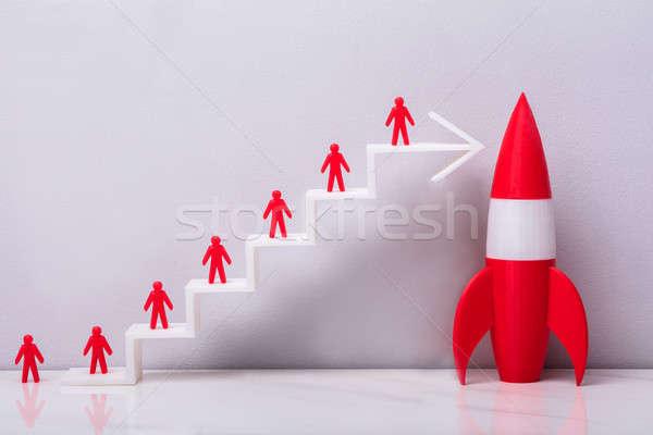 Stock photo: Red Rocket Beside Red Human Figure On Increasing Arrow