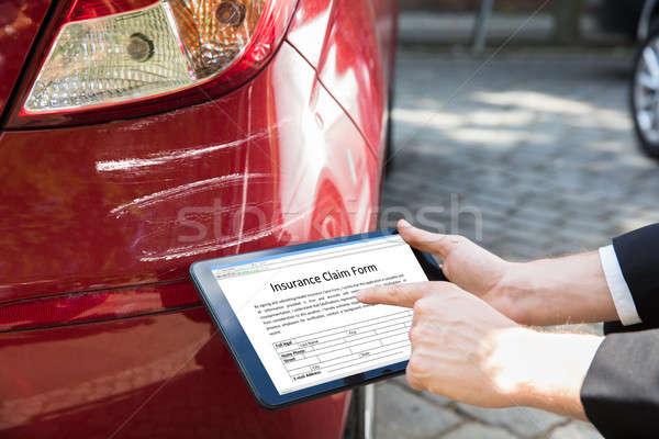 Person Filling Insurance Claim On Tablet Near Damaged Car Stock photo © AndreyPopov
